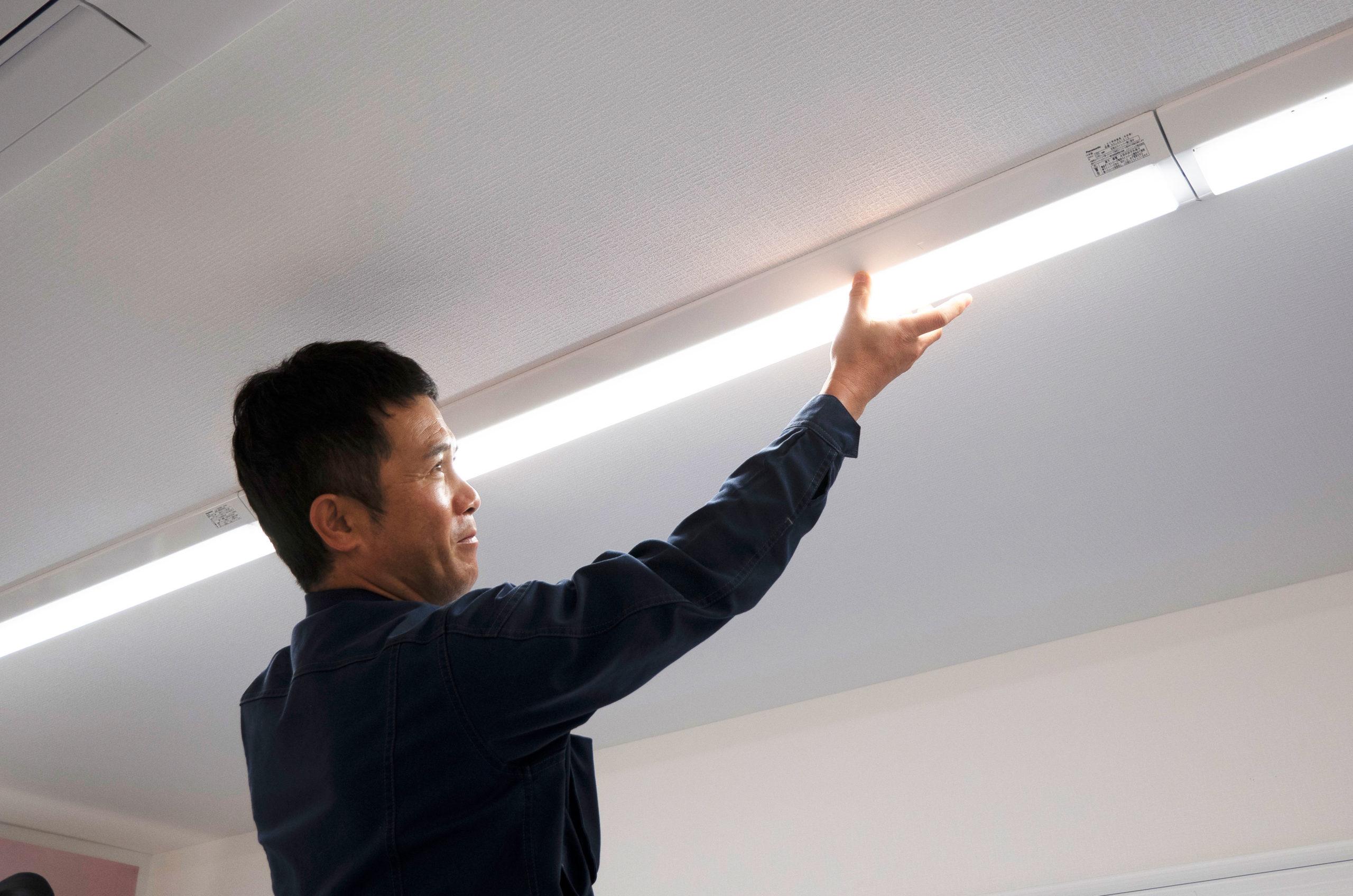 照明の修理点検をするスタッフ